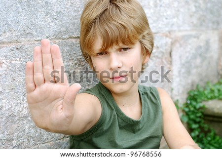 portrait of a boy with stopping hand outdoors - stock photo