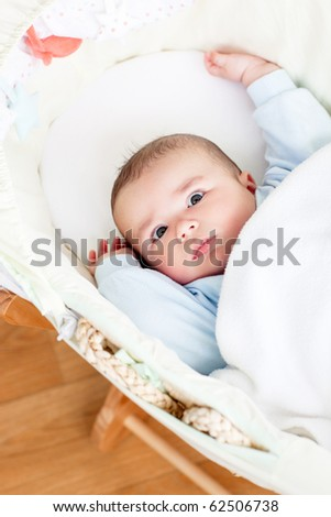 Portrait of a bright baby lying in his cradle at home - stock photo