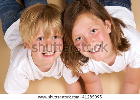 Portrait of a brother and sister in jeans and white shirts lying on the floor with wheat background