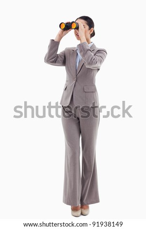 Portrait of a brunette businesswoman looking through binoculars against a white background - stock photo