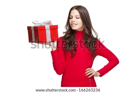 Portrait of a brunette christmas beauty holding shiny red gift box.