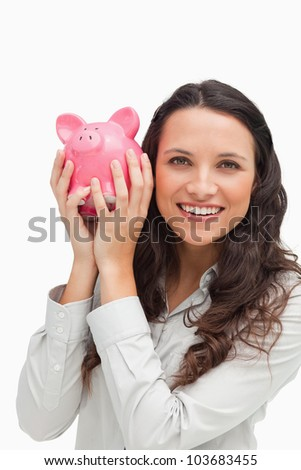Portrait of a brunette shaking a piggy bank against white background