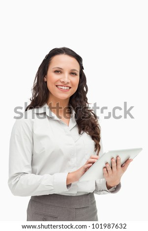 Portrait of a brunette standing while using a touchpad against white background - stock photo
