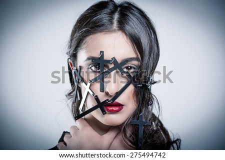 Portrait of a brunette with accessories in the form of crosses on the face
