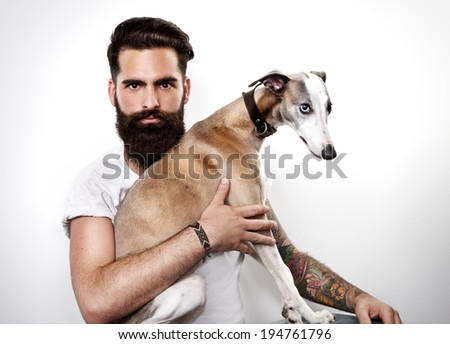 Portrait of a brutal bearded man with his dog - stock photo