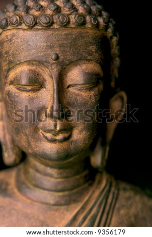 Portrait of a Buddha statue. Black background - stock photo