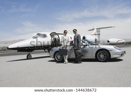 Portrait of a business couple standing in front of convertible and private jet on landing strip - stock photo