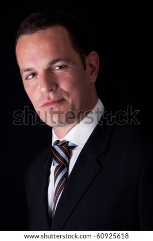 Portrait of a  business man isolated on black background. Studio shot. - stock photo
