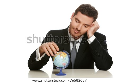 Portrait of a business man sitting by his desk and holding a globe model, isolated on white - stock photo