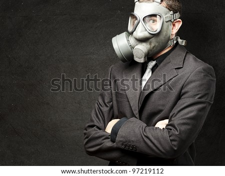 portrait of a business man with a gas mask against a grunge wall