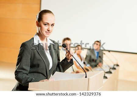 Portrait of a business woman holding a microphone and looks to the camera