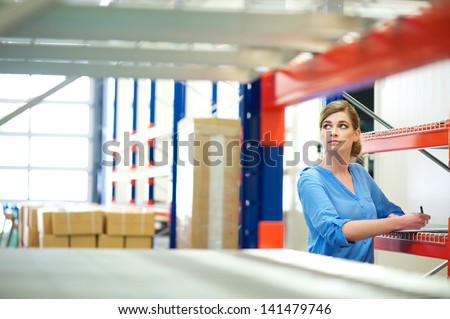 Portrait of a business woman inspector doing inventory in a warehouse - stock photo