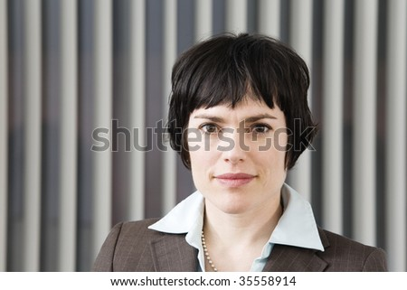 Portrait of a business woman with vertical blind in background. - stock photo