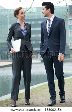 Portrait of a businessman and business woman walking together outdoors - stock photo