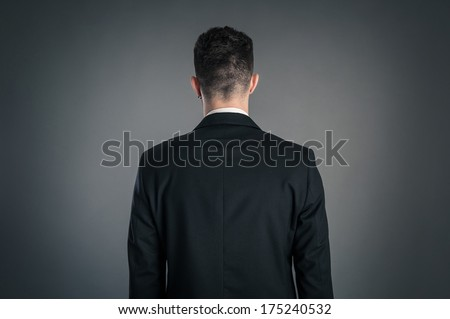 Portrait of a businessman back view isolated on dark background. Studio shot.  - stock photo