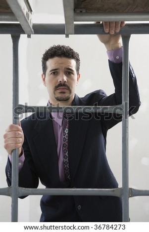 Portrait of a businessman climbing scaffolding - stock photo