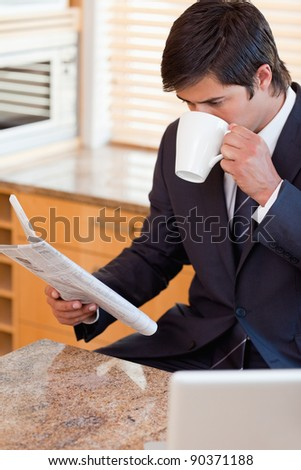 Portrait of a businessman drinking coffee while reading the news in his kitchen - stock photo