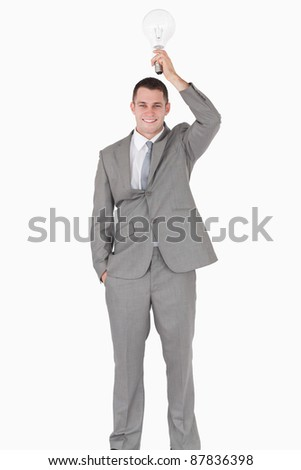 Portrait of a businessman holding a bulb above his head against a white background