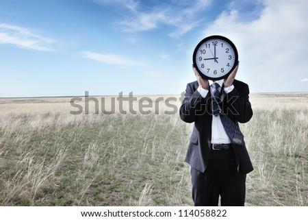 Portrait of a businessman holding a clock on grassland - stock photo