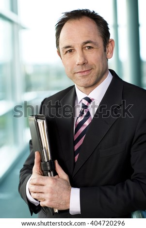 Portrait of a businessman holding a leather case with briefing papers - stock photo