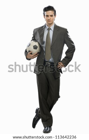 Portrait of a businessman holding a soccer ball - stock photo