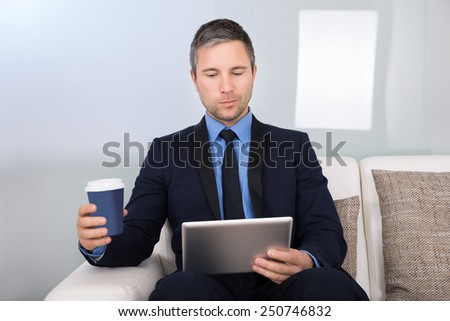 Portrait Of A Businessman Holding Disposable Coffee Cup Looking At Digital Tablet - stock photo