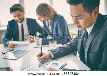 Portrait of a businessman in board room analyzing charts  - stock photo