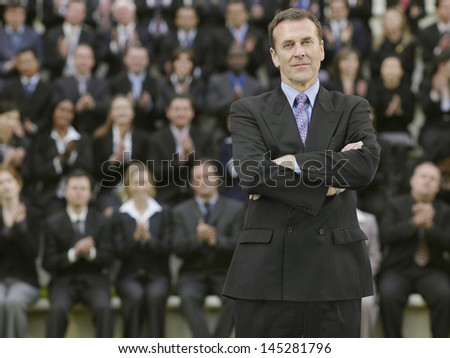 Portrait of a businessman in front of blurred multiethnic businesspeople - stock photo