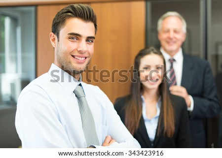 Portrait of a businessman in front of his colleagues - stock photo