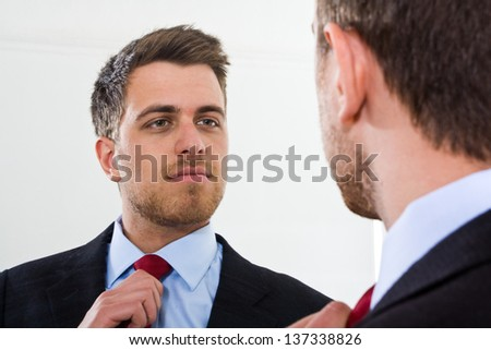 Portrait of a businessman looking at himself in the mirror - stock photo