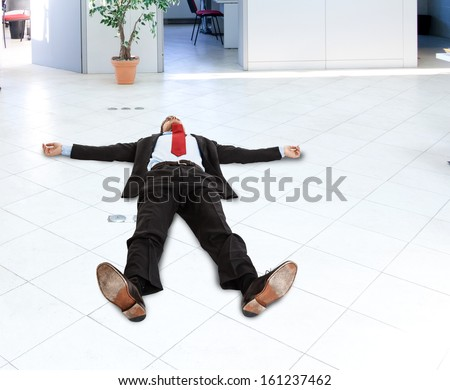 Portrait of a businessman lying on the floor - stock photo