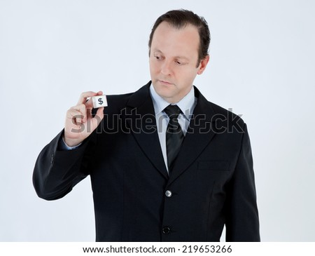 Portrait of a businessman, mature, bald, wearing a suit and tie, holding a cube with a dollar sign on white background