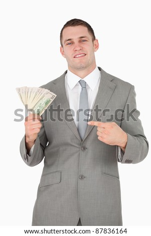 Portrait of a businessman pointing at a wad of cash against a white background - stock photo