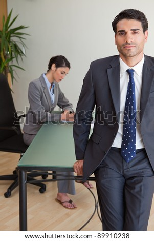 Portrait of a businessman posing while his colleague is working in an office - stock photo