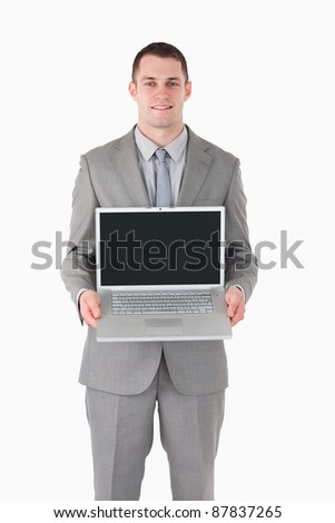 Portrait of a businessman showing a laptop against a white background - stock photo
