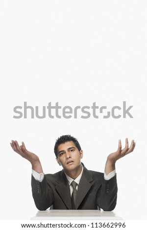 Portrait of a businessman shrugging - stock photo