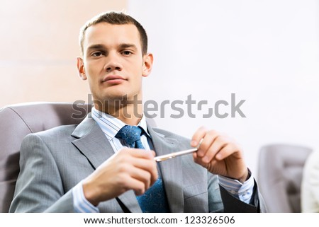 Portrait of a businessman sitting at a table and holding a pen