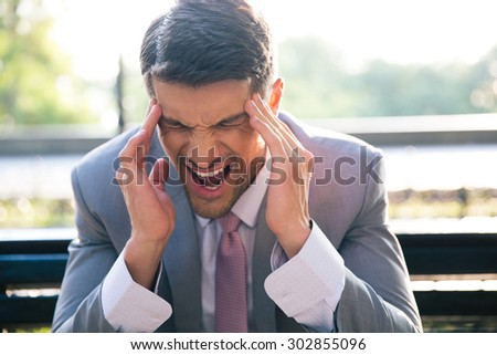 Portrait of a businessman sitting on the bench outdoors and having headache - stock photo