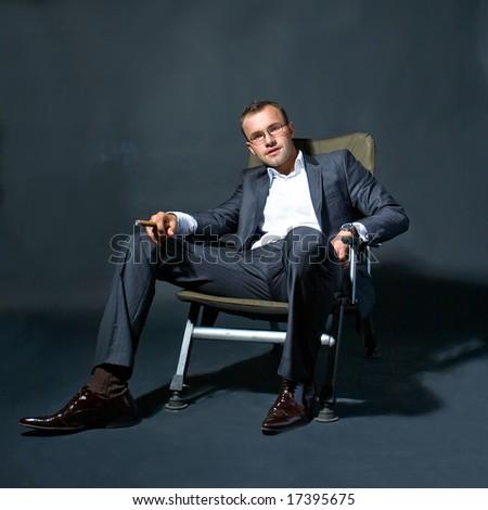 Portrait of a businessman smoking a cigar - stock photo