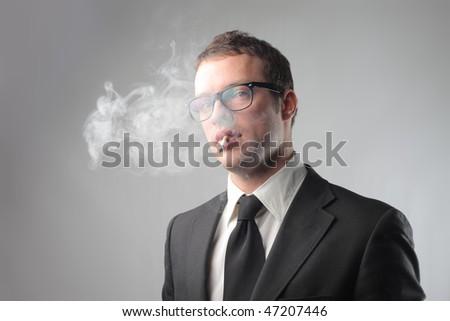Portrait of a businessman smoking a cigarette - stock photo