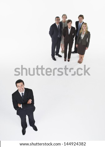 Portrait of a businessman standing apart from group against white background