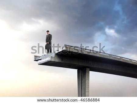 Portrait of a businessman standing on an interrupted highway bridge and looking into the empty space underneath - stock photo