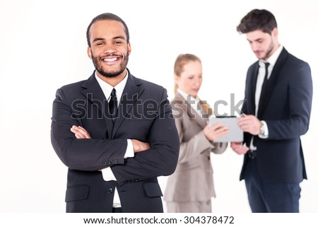 Portrait of a businessman. Successful African businessman standing with hands clasped while colleagues are working on a computer in the background on a gray background - stock photo