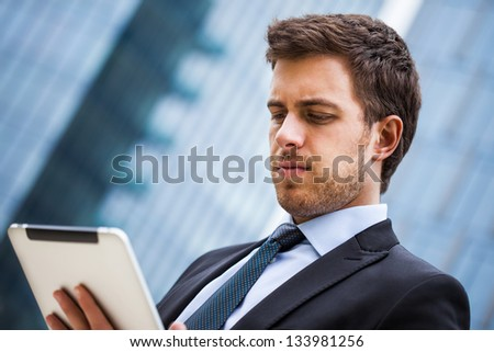 Portrait of a businessman using a tablet pc - stock photo