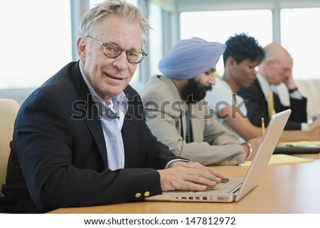 Portrait of a businessman using laptop besides multiethnic colleagues in conference room - stock photo