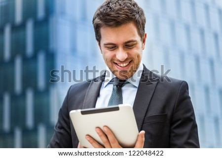Portrait of a businessman working on his tablet - stock photo