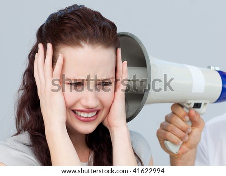 Portrait of a businesswoman getting nervous with a megaphone next to her