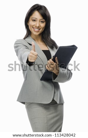 Portrait of a businesswoman holding a file and showing thumbs up - stock photo