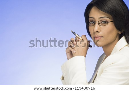 Portrait of a businesswoman holding a pen - stock photo