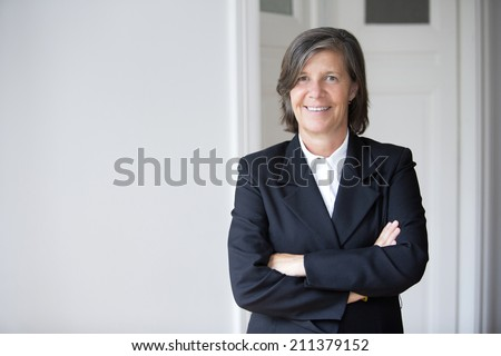 Portrait of a businesswoman in a suit and smiling - stock photo